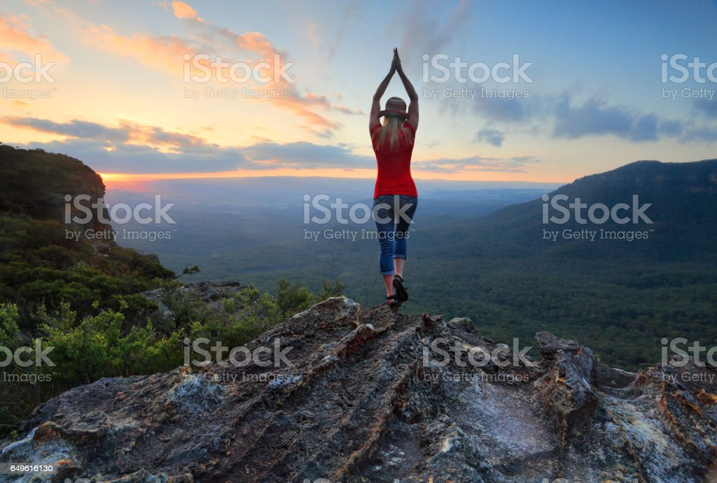 Female fitness stretch to the sky mountain top valley scene stock photo