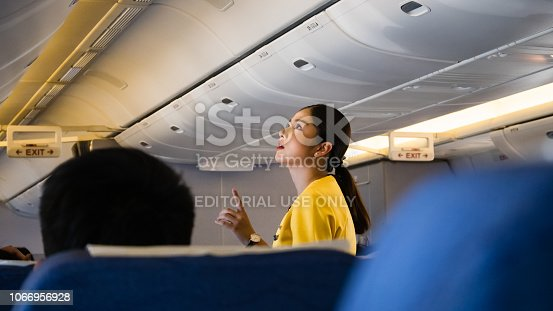 istock A female flight attendant is assisting a passenger in the economy class of the route Bangkok - Tokyo of Nok scoot Airline. 1066956928