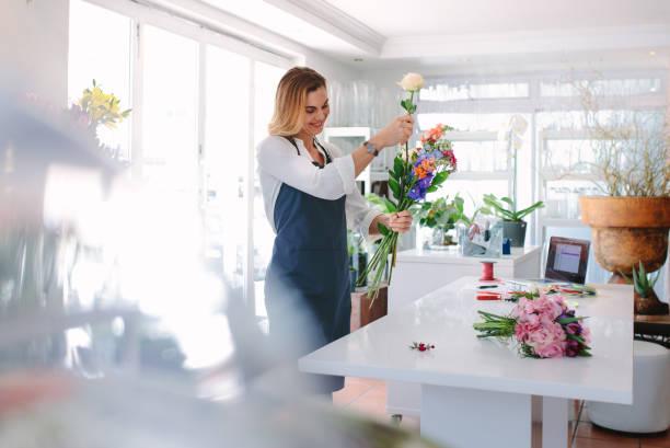 femme fleuriste création d'ordre - fleuriste photos et images de collection