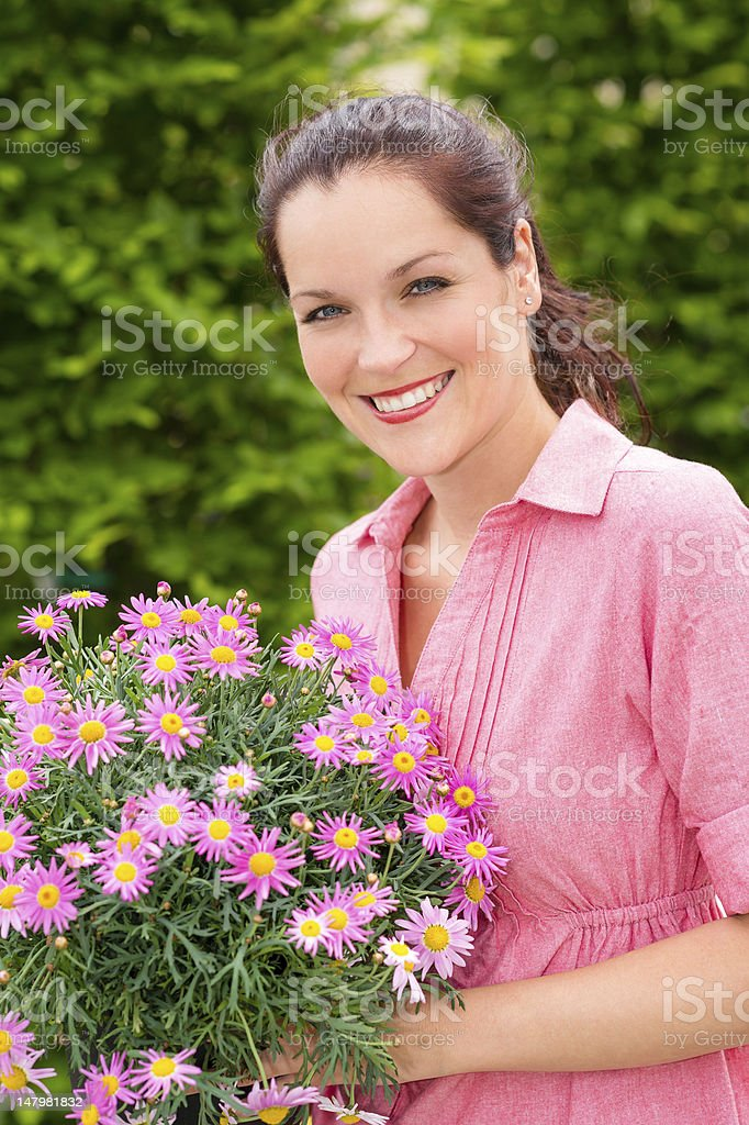 Female florist hold pink potted flower royalty-free stock photo