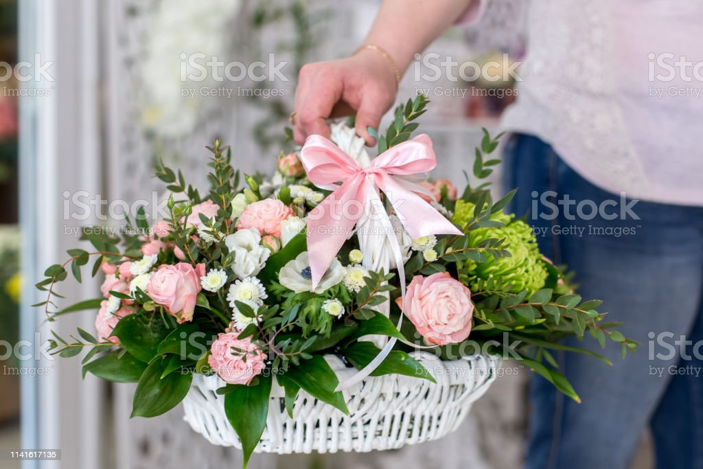 Female Florist holding a beautiful bouquet of roses in white basket....
