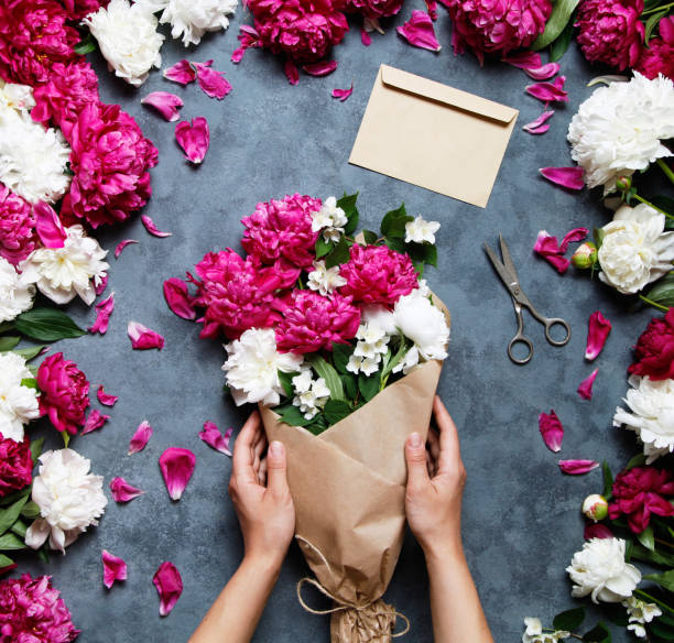 Female florist holding beautiful bouquet at flower shop. Florist at work: pretty woman making summer bouquet of peonies on a working gray desk. Kraft paper, scissors on the table. stock photo