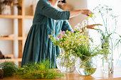 スタジオにハーブの花束を作る女性の花屋