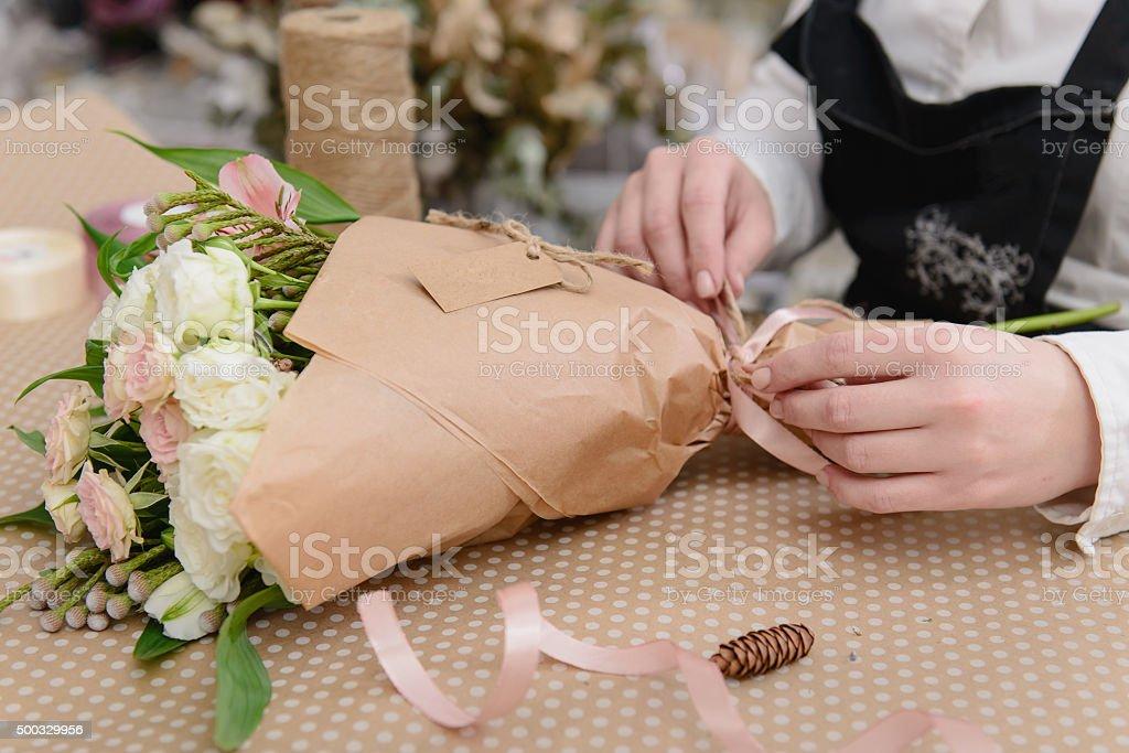 Crème femme fleuriste fait un bouquet de roses sur la table. - Photo