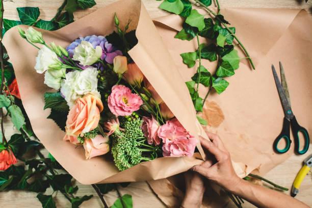 Female florist making flower bouquet stock photo