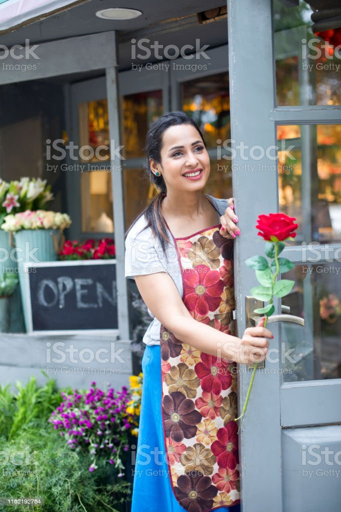 Happy female florist holding red rose in flower shop doorway
