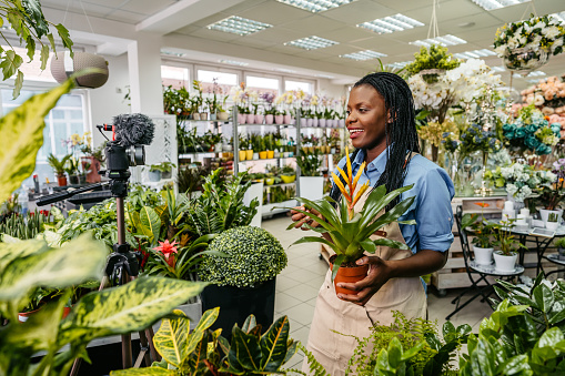 Female florist making vlog session while working in her flower shop.