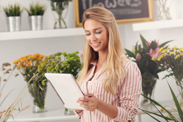 weibliche florist arbeiten im blumenladen mit tablet - hochzeitskleider online stock-fotos und bilder