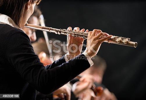 Female flutist performing, hands close-up on dark background.