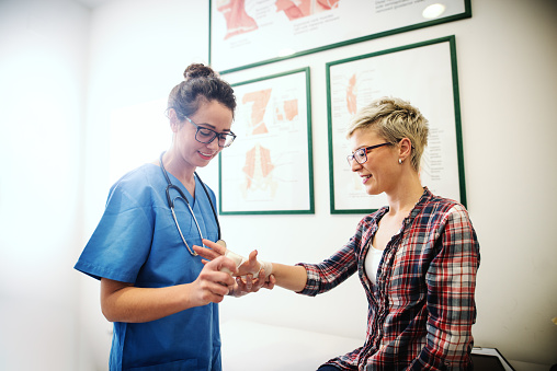 istock Female folding broken arm while patient sitting on bed. Around doctor's neck stethoscope. 1073909084