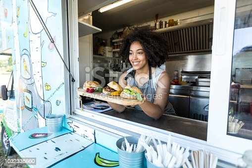 Smiling female food vendor offering sandwiches and burgers in food van.