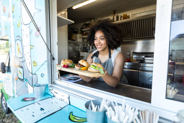 Female food vendor offering sandwiches in food van Smiling female food vendor offering sandwiches and burgers in food van. food truck stock pictures, royalty-free photos & images