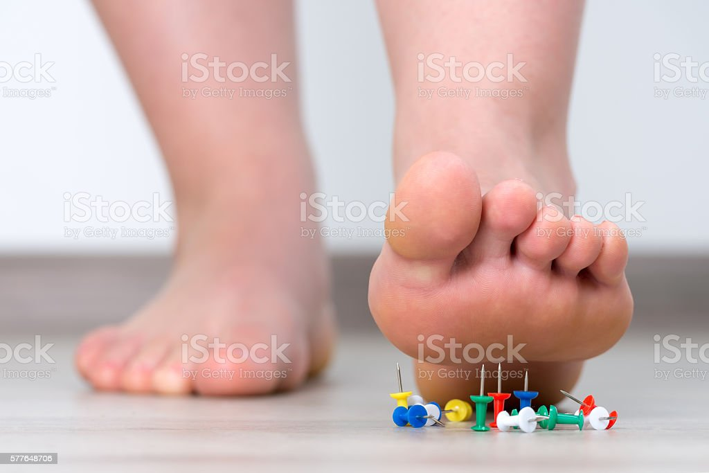 Female foot above colored pushpin stock photo