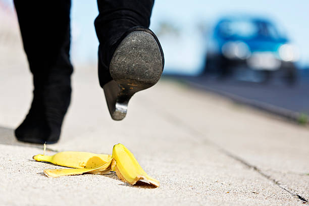 Female foot approaches banana skin; painful accident coming her way An unidentified  female walker's foot in high-heeled boots is about to step on a dropped banana peel. A painful fall coming in 3, 2, 1...  banana peel stock pictures, royalty-free photos & images