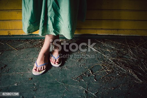 959792752 istock photo Female foot in slippers on wooden background 625801298