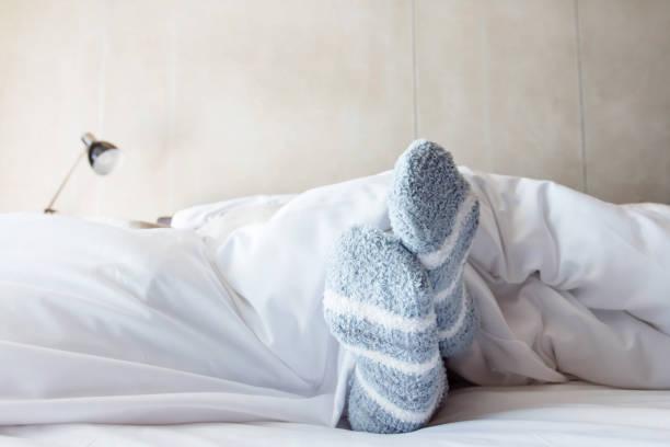 Female foot in warm Stripe wool sock stock photo
