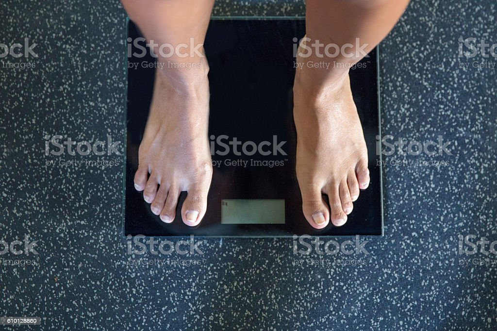 Female foot on weight scale - foto de stock