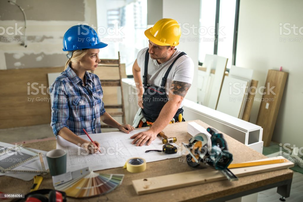 Female foreman and manual worker talking while analyzing blueprints at construction site. stock photo