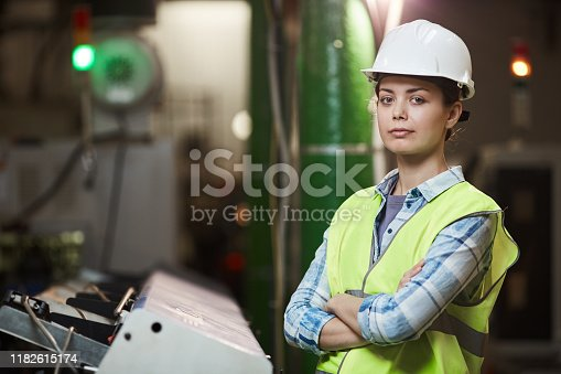 Portrait of female foreman in protective workwear standing with arms crossed and looking at camera while working in the plant