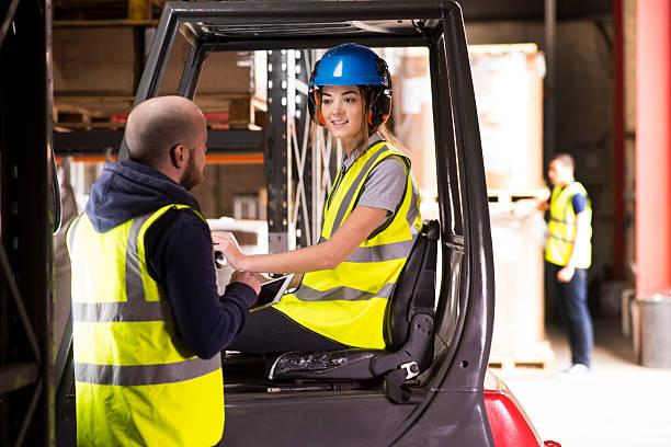 conductor de carretilla elevadora hembra charlar al supervisor de almacén. - suministros escolares fotografías e imágenes de stock