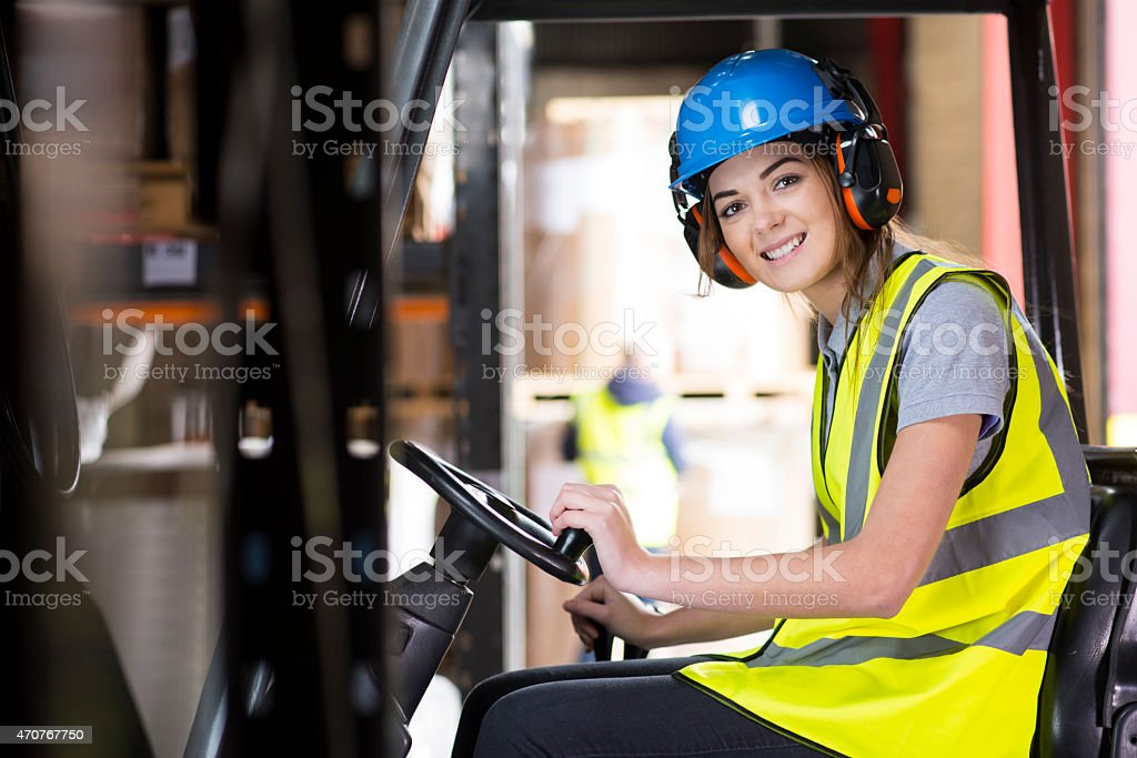 female forklift driver in a warehouse stock photo
