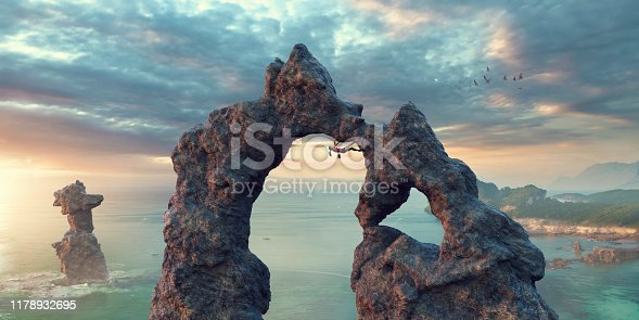 A wide angle panoramic image of a female extreme free climbers upside down, traversing the underside of a huge natural rock arch. The climber is wearing a top, shorts, climbing shoes and chalk bag . The location is fictional, by the sea as the dawn sun rises.