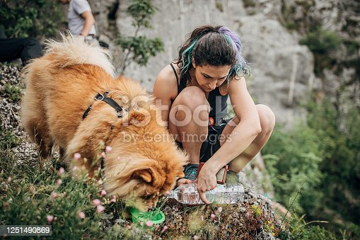 One woman, free climber, giving water to dog in nature.