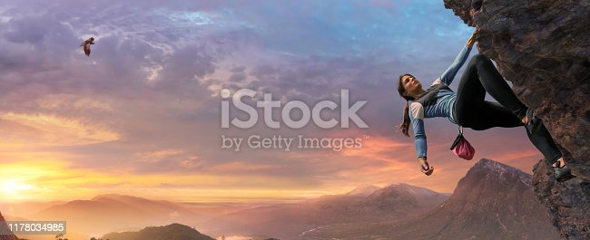 A female free climber wearing climbing shoes, leggings, top and chalk bag scaling an inclined rock face at high altitude under a beautiful dawn sky.  The climber has two feet and one outstretched arm in contact with the rock face and is leaning back with other arm relaxed.