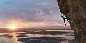 A young female free climber dressed in leggings, long sleeved climbing top, climbing shoes and chalk bag high up on a steep sheer rock face. The climber is in a coastal location as the morning sun rises over water and small islands. With selective focus on the climber.