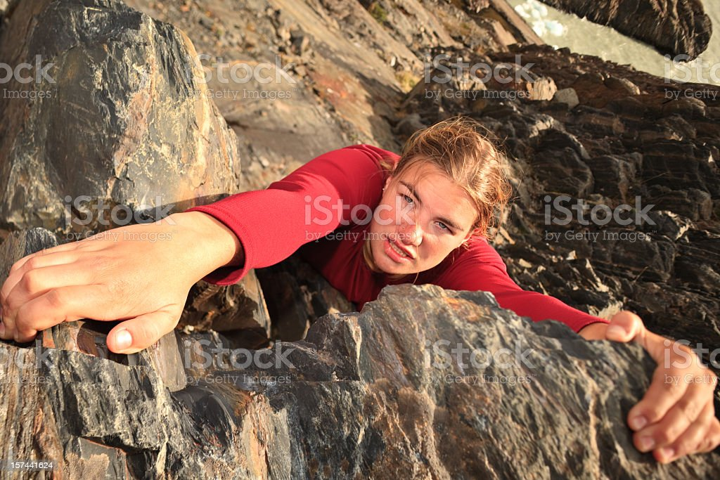 A female free climbing up the side of a mountain  stock photo