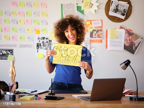 Female freelance creative for hire, holding a sign in her remote home office.