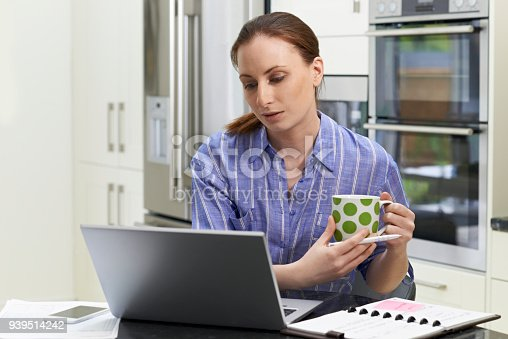 Female Freelance Worker Using Laptop And Drinking Coffee In Kitchen At Home