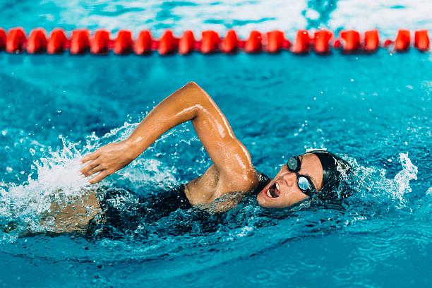 female frestyle swimmer - wedstrijdsport stockfoto's en -beelden