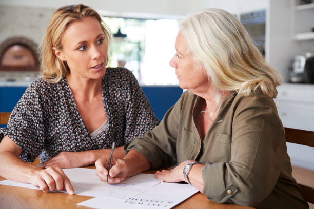 Female Friend Helping Senior Woman To Complete Last Will And Testament At Home Female Friend Helping Senior Woman To Complete Last Will And Testament At Home last stock pictures, royalty-free photos & images