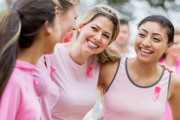 arkadaşlar sadaka yarış sırasında bağ - breast cancer awareness stok fotoğraflar ve resimler