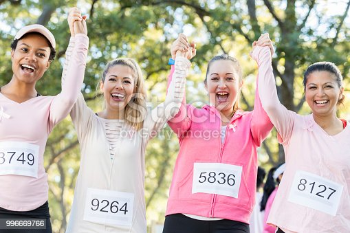 Beautiful friends hold hands and cheer after finishing a breast cancer awareness race.