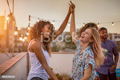 Cheerful women dancing with arms raised during party. Happy female friends are enjoying on terrace. Multi-ethnic people are celebrating during sunset.