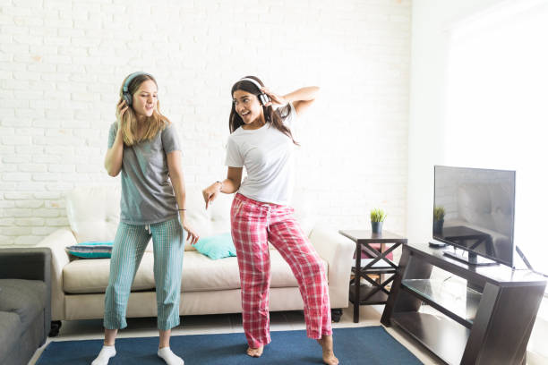 Female Friends Dancing While Listening To Music On Headphones stock photo