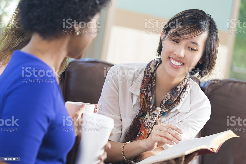 Female friends discussing scripture during home bible study stock photo