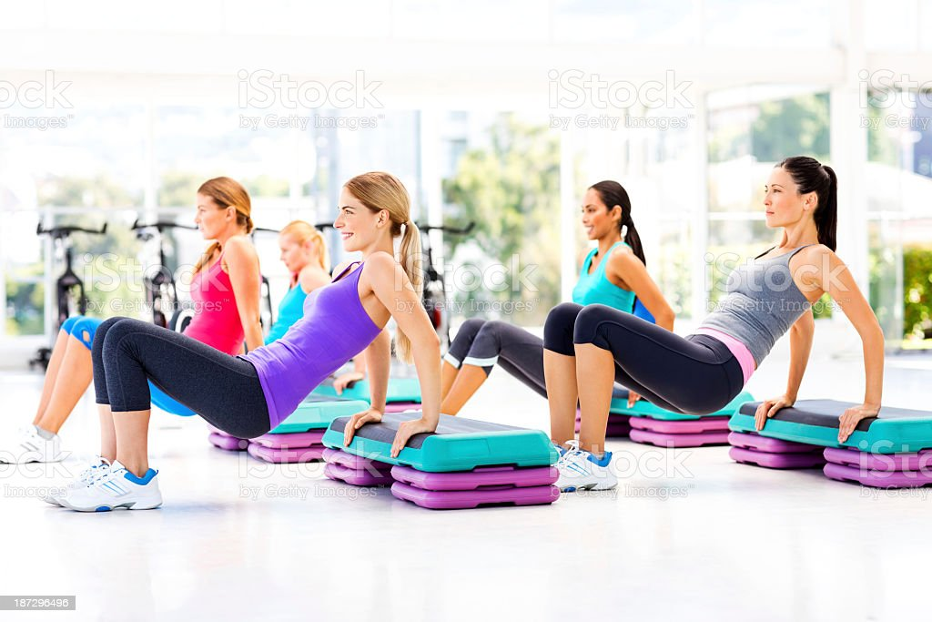 Female Friends Doing Step Aerobics In Gym stock photo