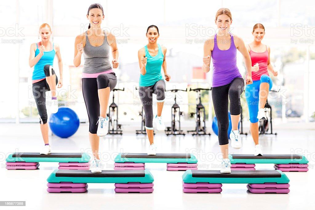 Female Friends Doing Step Exercise In Health Club stock photo