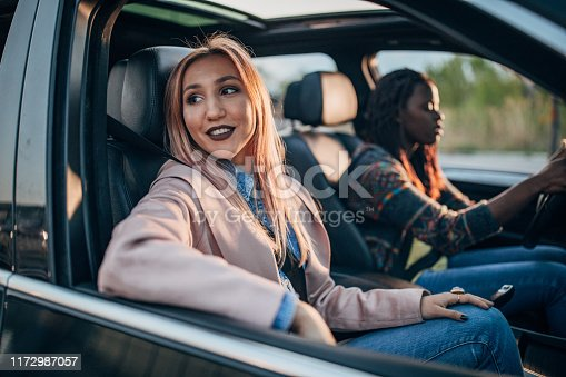 812419994istockphoto Female friends driving in a car 1172987057
