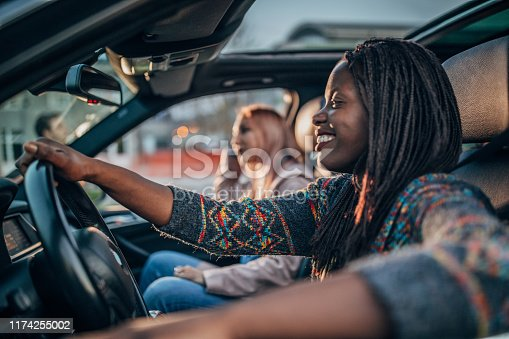 812419994istockphoto Female friends driving in a car 1174255002