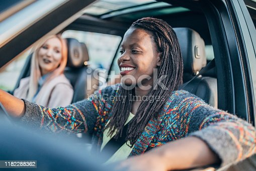 812419994istockphoto Female friends driving in a car 1182288362
