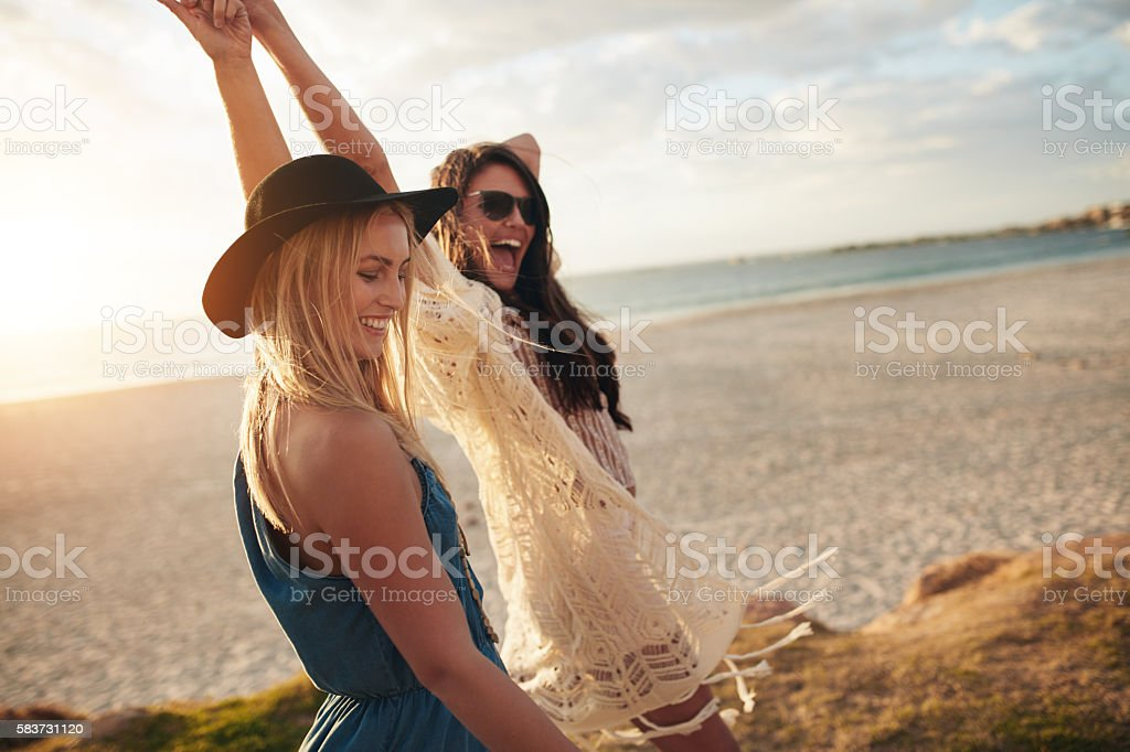 Female friends enjoying a day at sea coast stock photo