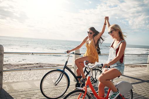 Female friends enjoying cycling on a summer day