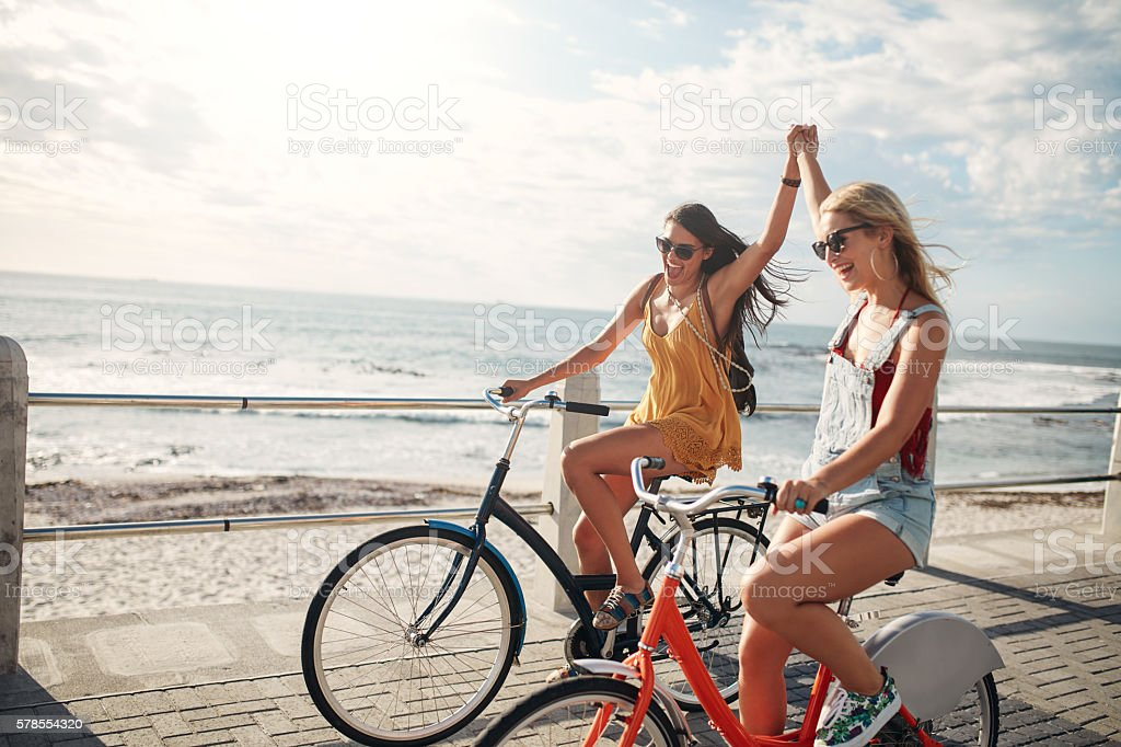 Female friends enjoying cycling on a summer day stock photo