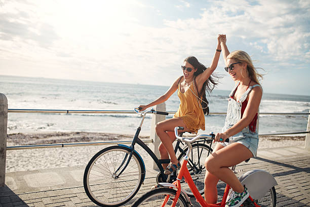 female friends enjoying cycling on a summer day - bisiklet stok fotoğraflar ve resimler