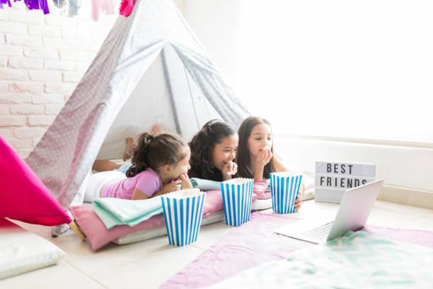 freundinnen snacks genießen, beobachten laptop im zelt - tipi zelt stock-fotos und bilder