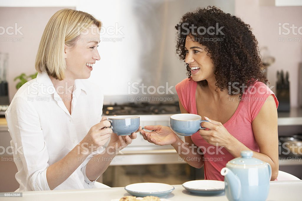 Female Friends Enjoying Tea And Cookies At Home stock photo